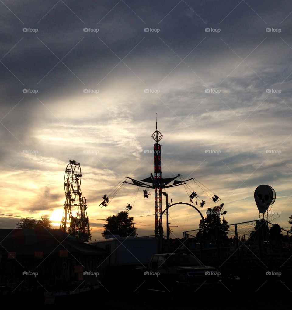 Fair festival rides in Ohio during sunset on skyline. Ferris wheels and carnival rides