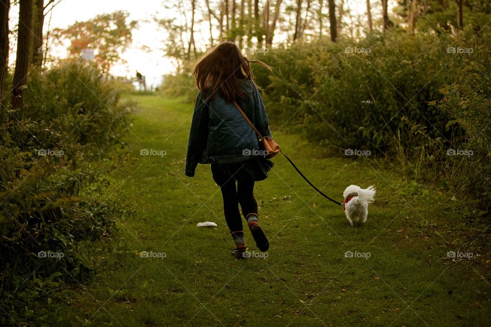 Girl walking her puppy into a forest at sunset