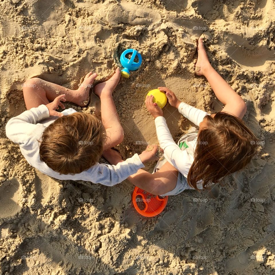 Boy and girl playing in the sand on the beach