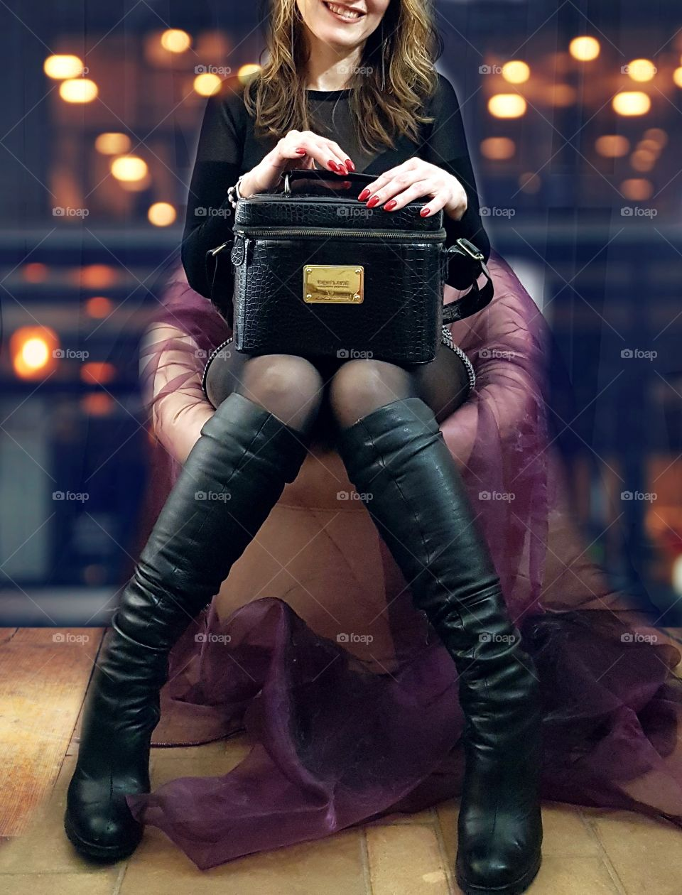 A beautiful girl in boots sits in a chair and holds a black suitcase