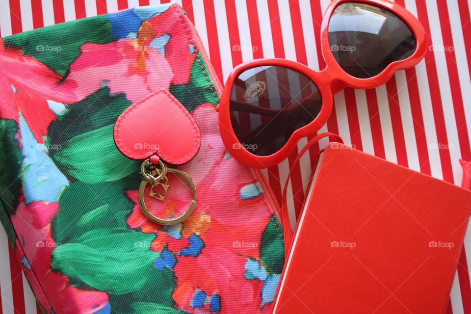 Red and white stripes, makeup bag, heart-shaped sunglasses, notebook and heart-shaped key ring flat lay.