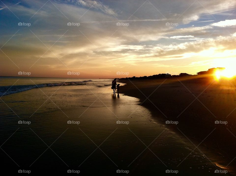 Mother and daughter strolling on the peaceful beach during sunset at Emerald Isle North Carolina