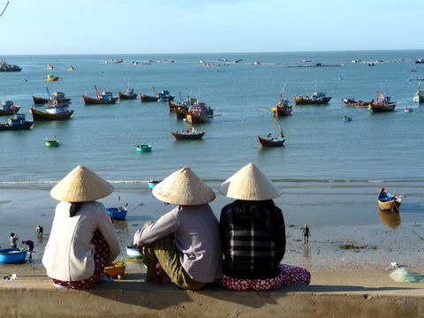 Women sitting with conical hat at beach side