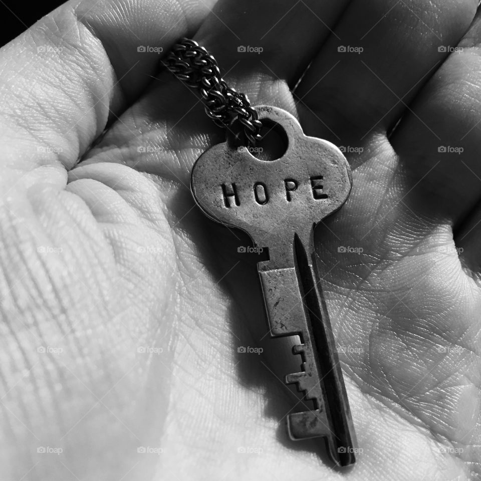 A black and white close up photo of a hand holding a metal key necklace. The key has the word 'hope' engraved on it