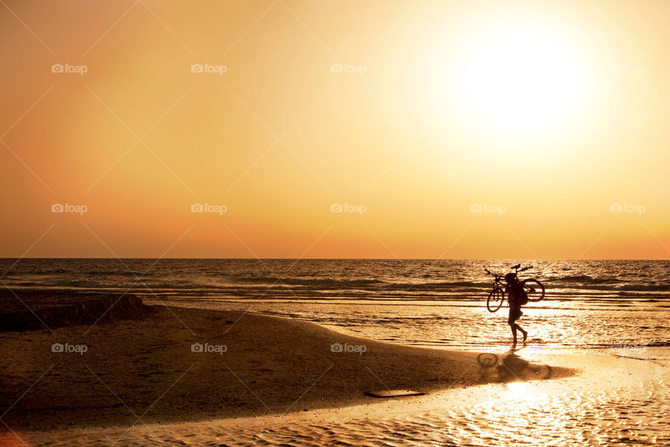 A person carrying bicycle on beach