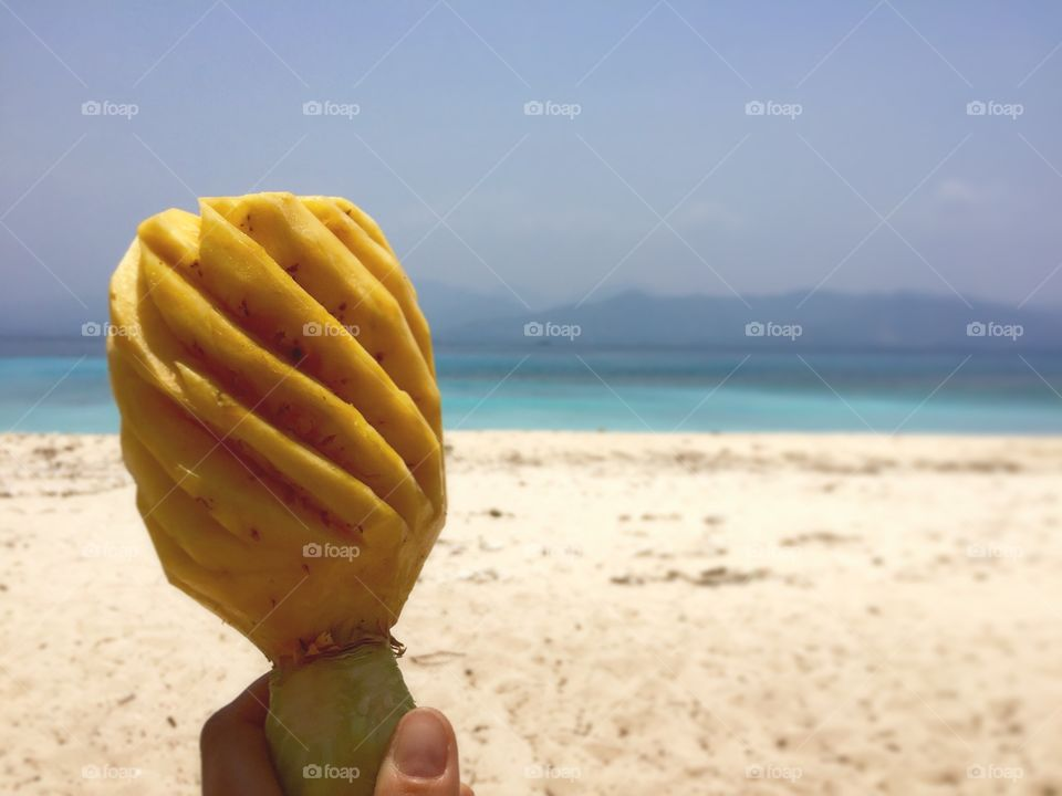 Person holding peeled pinapple