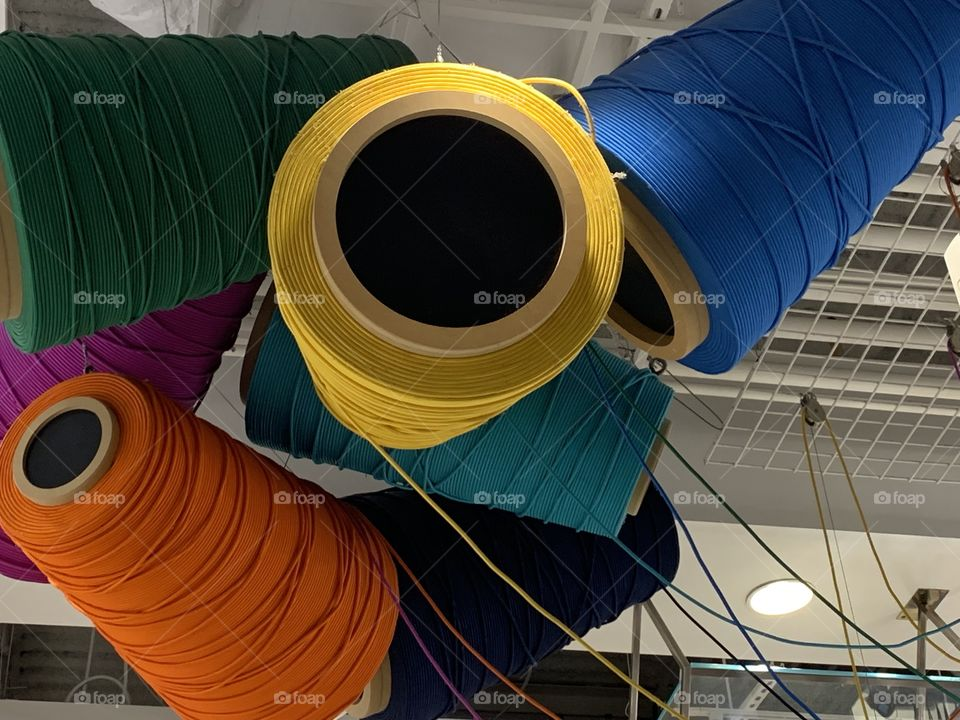 Decor of different color rolls of string.  Larger than life.  Look up