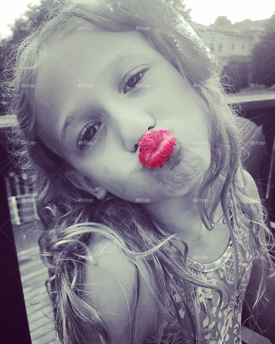Black and white photo of a little girl with bright pink glittery lips. Pucker up!