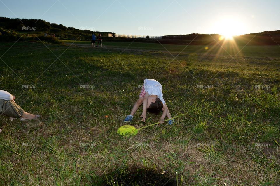 a boy playing in the grass in the field during the sunset
