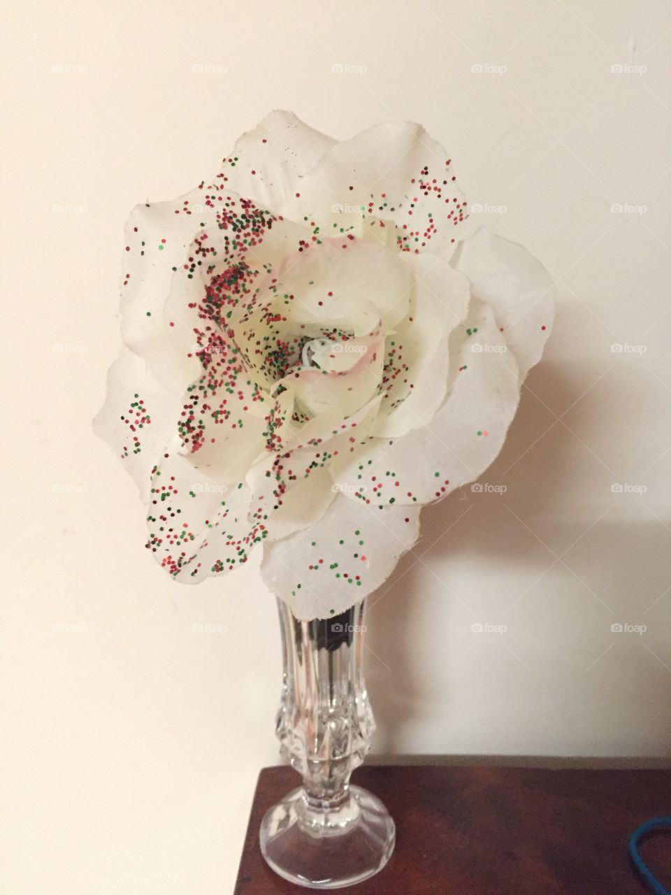 White rose with glitter in a glass vase