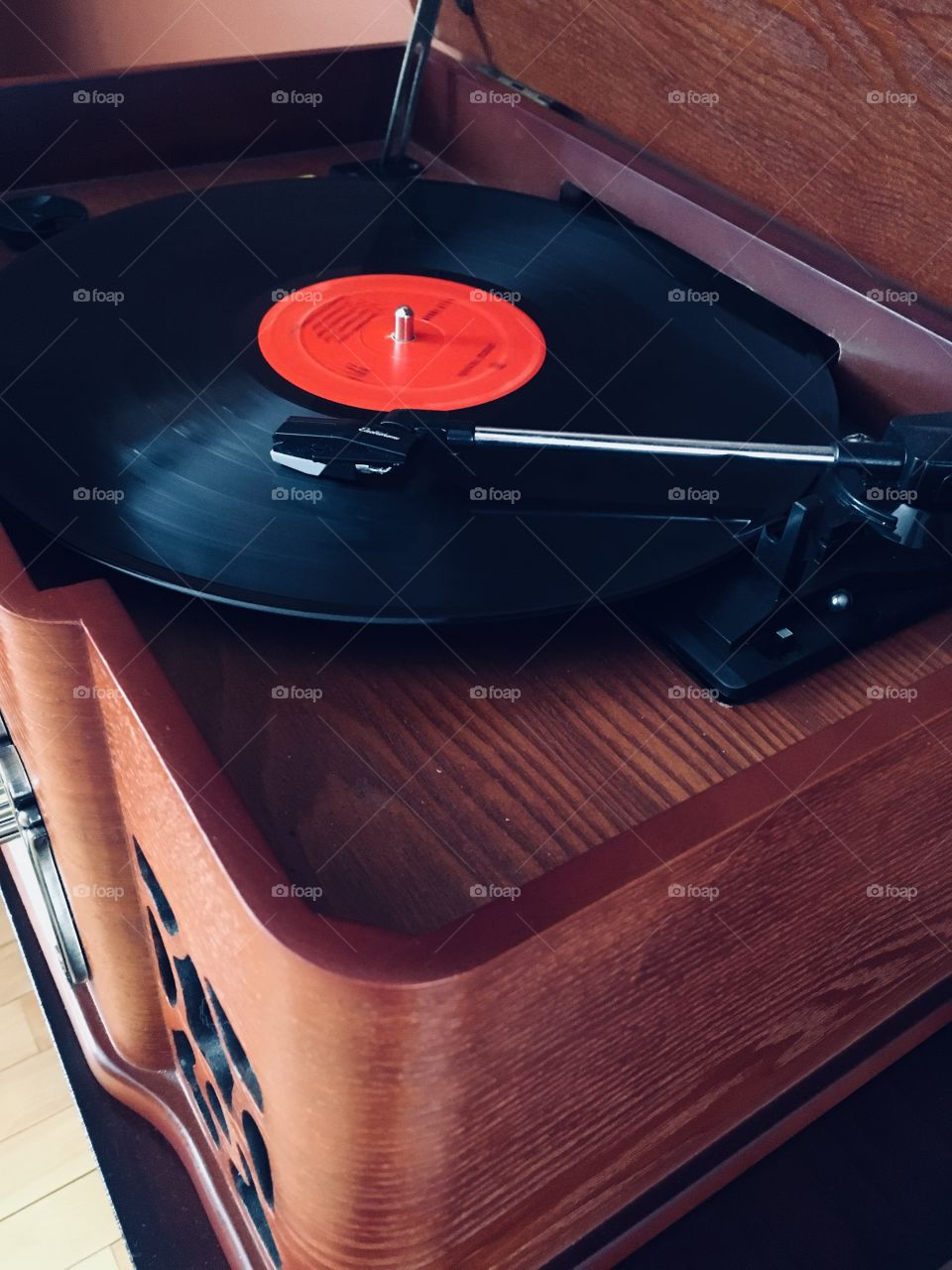 Vinyl record playing music on a vintage antique style wooden record player.
