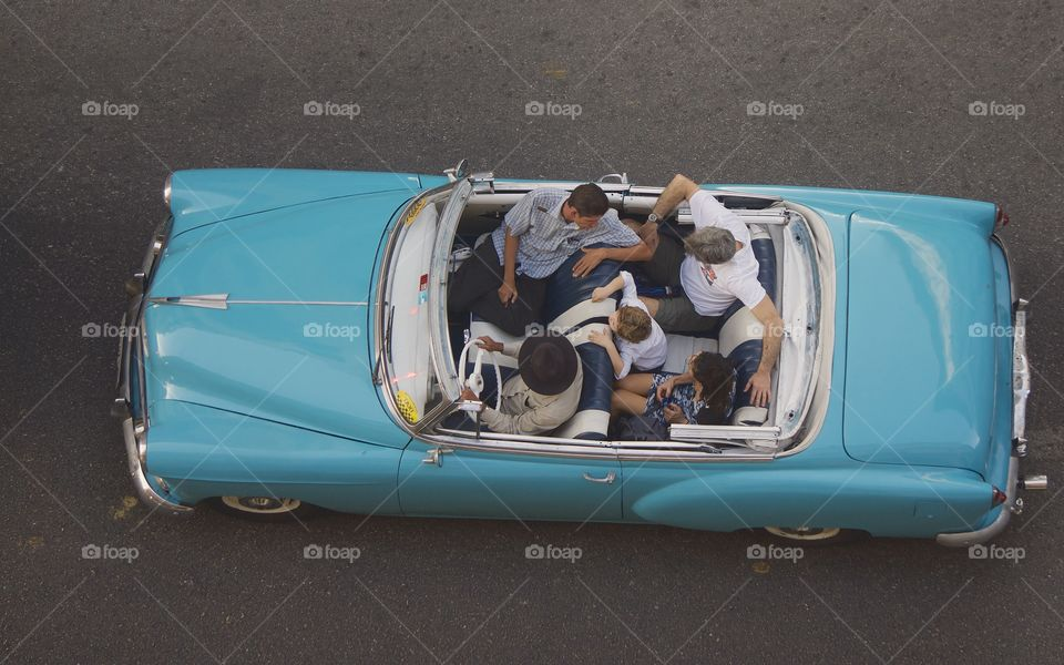 A bird's eye view from a rooftop of a classic American car in Old Havana, Cuba