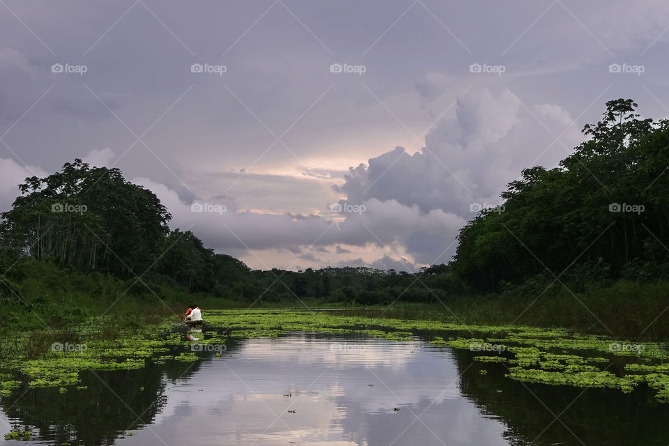 Piranha fishing on amazon river. Sunset through stormy cloudy skies. Two fisherman, near Iquitos Peru.