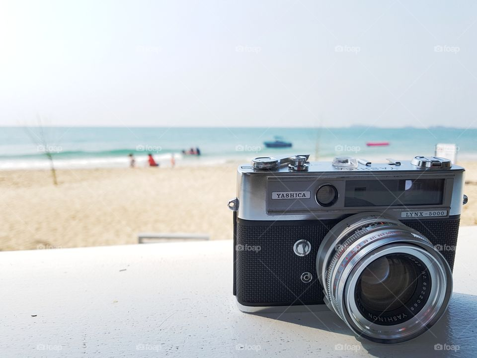 traveler retro vintage film camera on the beach