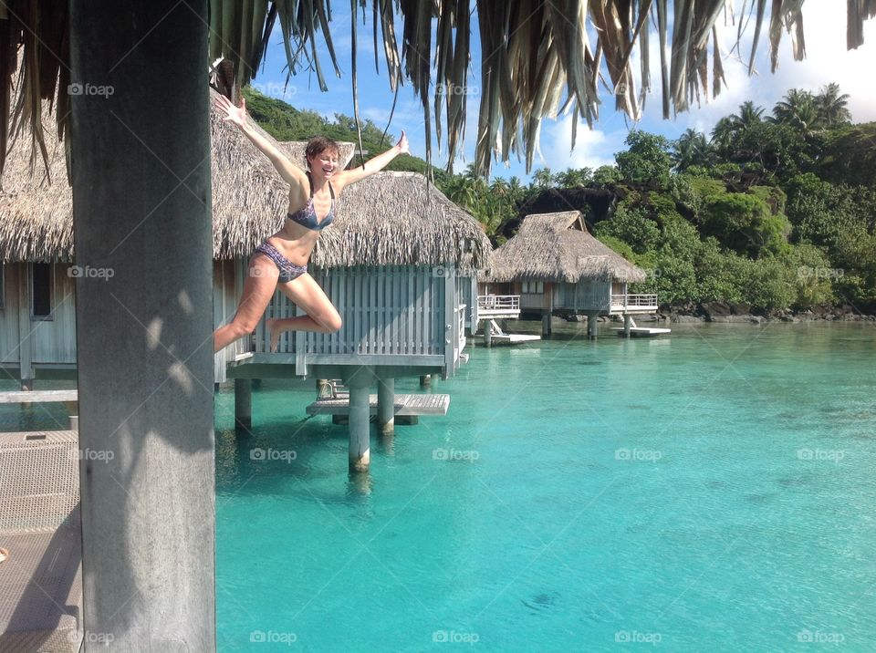 Jumping in the water. Bora Bora hut over water