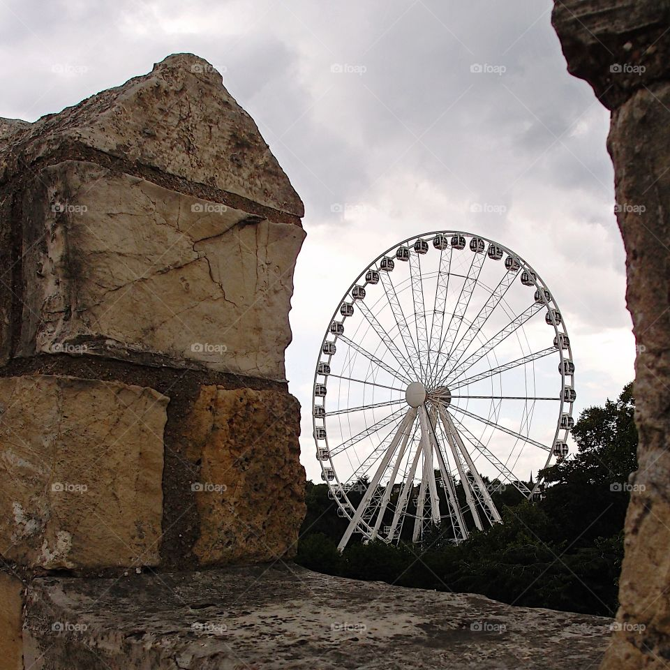 The York Wheel viewed through the historic York Wall in England on a summer day.