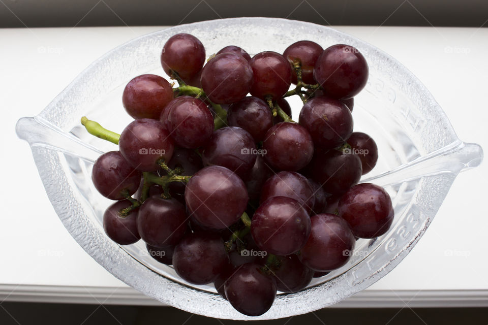 Colorful red grapes in glass bowl