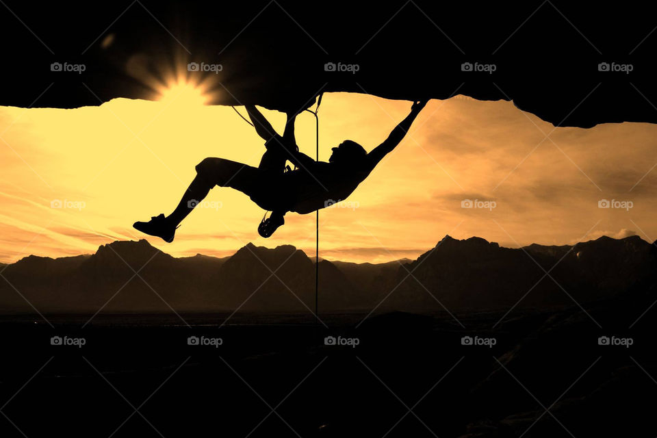 Silhouette of a person climbing on rock