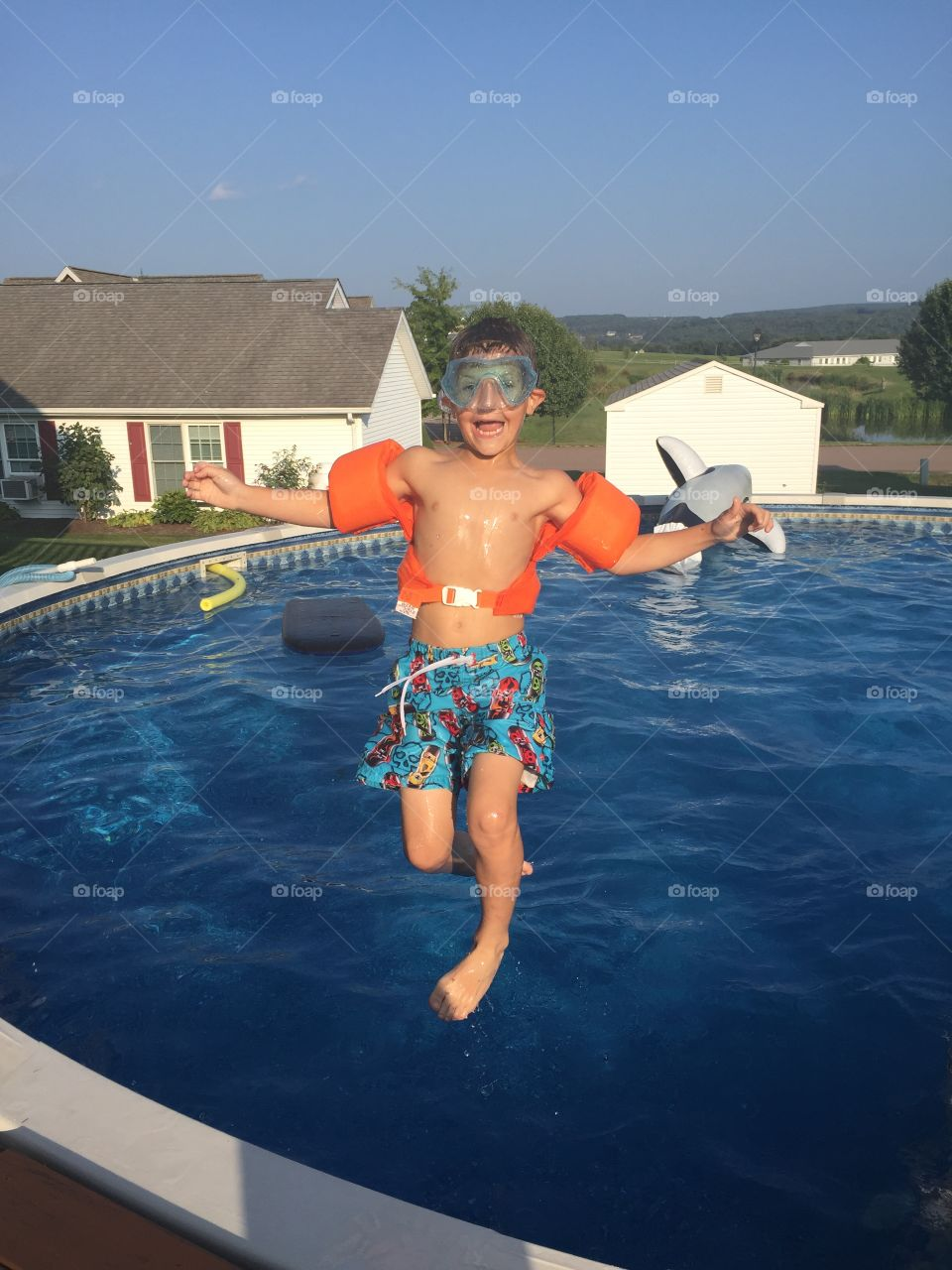 Happy boy jumping in swimming pool