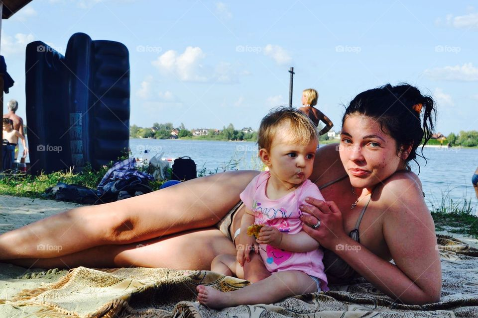 Baby and mother at the lake beach