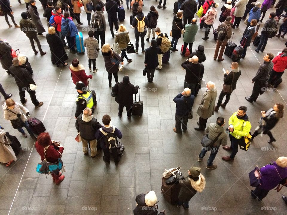 Looking down on the crowded concourse of a busy railway station as. Roads of rail commuters and passengers wait for their train at Kings Cross in London.
