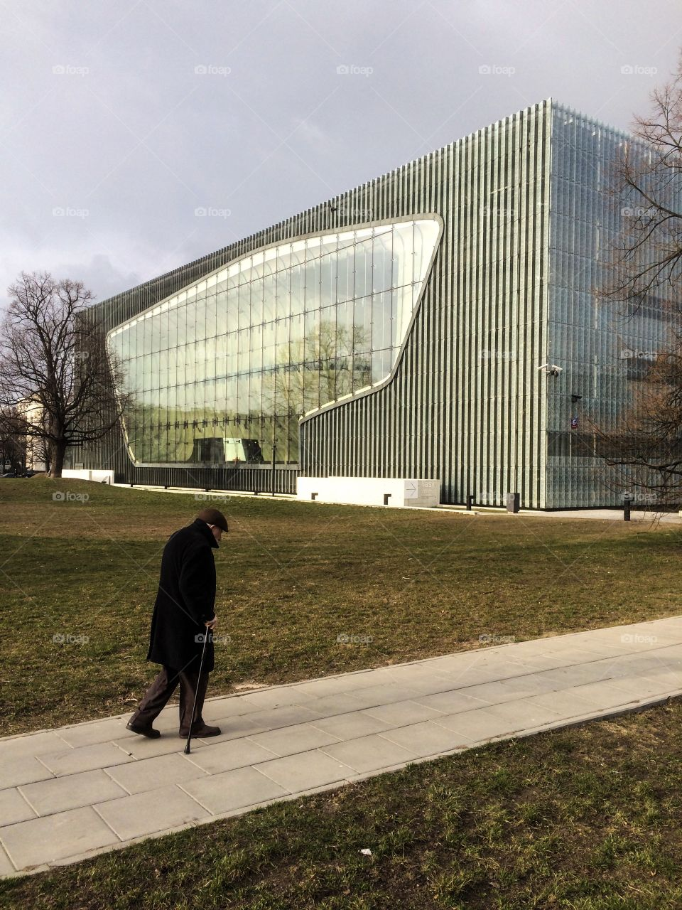 An old man walking near the modern building of Museum of Polish Jews in Warsaw in a cold day. View from behind.