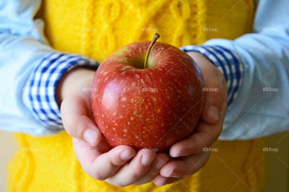Kid holding ripe red apple