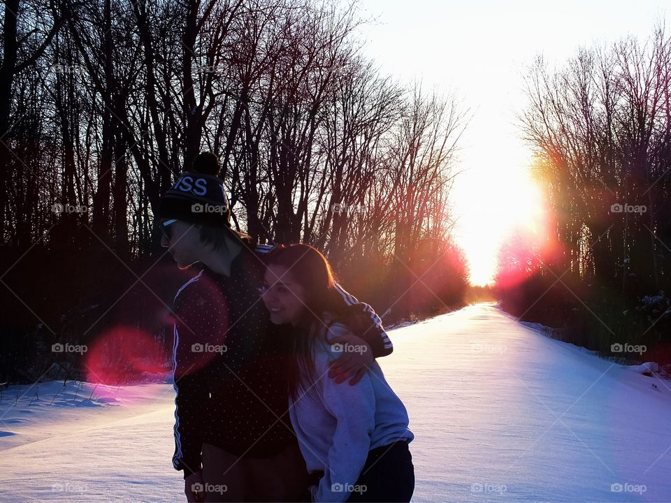 Couple at sunset on snow covered railroad tracks beautiful sunset in winter