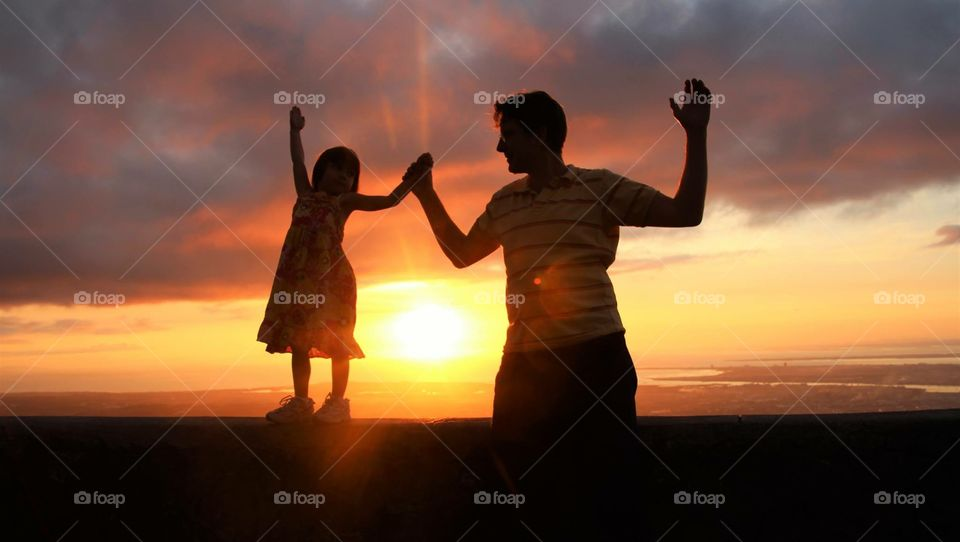 Father with her daughter raising arms at sunset