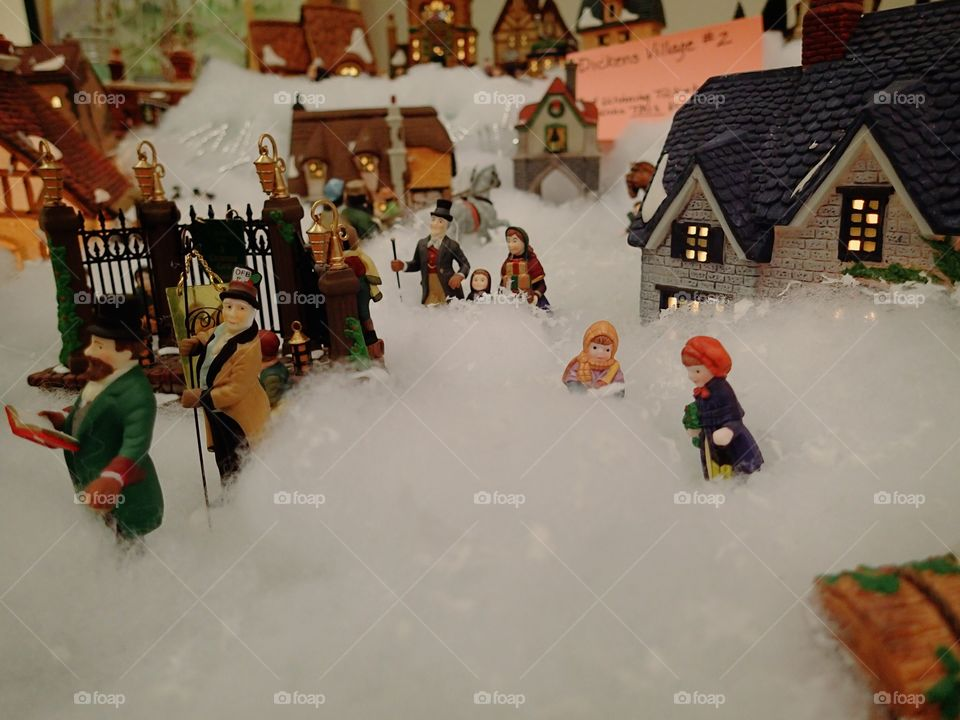 a Christmas village with characters dressed in the Victorian era.
