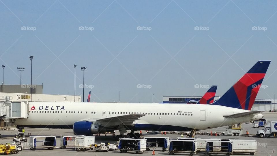 Delta airlines plane parked with luggage carts