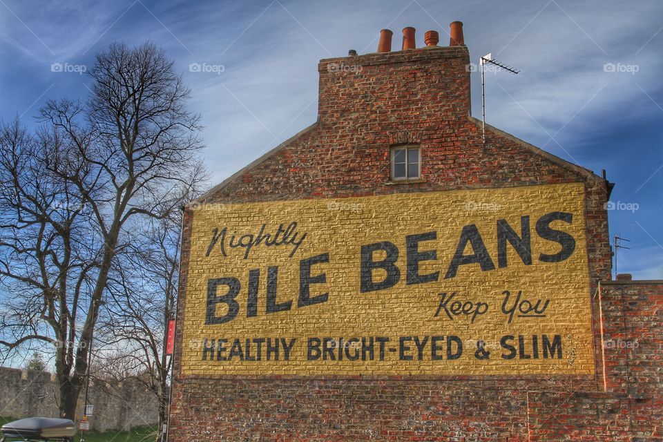 An antique advert painted on the side of a brick building in York.
