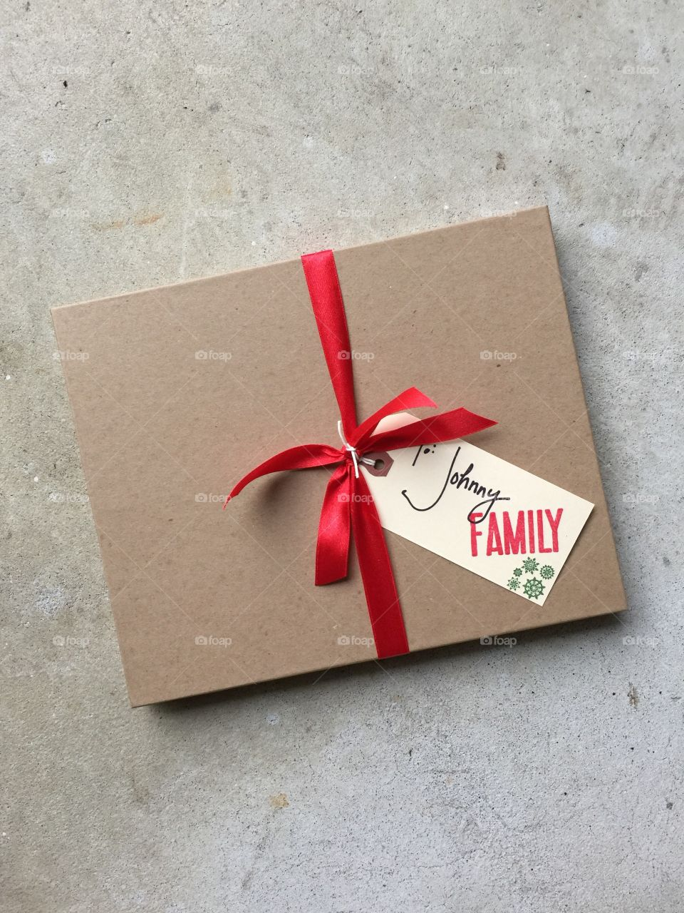 Brown rectangular craft cardboard gift box tied with single red festive ribbon and gift tag with handwriting family