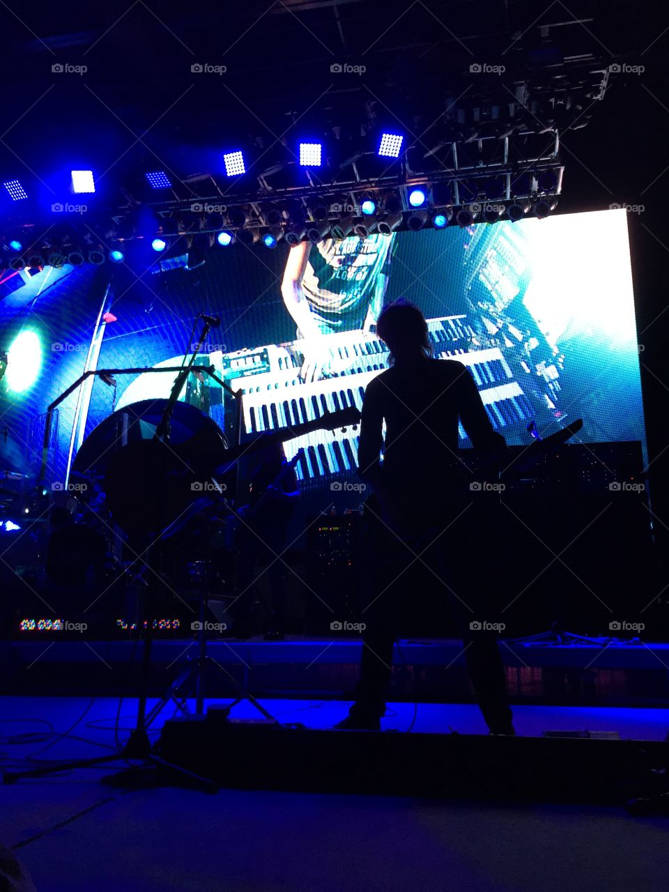 Boston guitarist Tom Scholz on stage, performing a keyboard solo against a video backdrop at the Saint Augustine amphitheater in Florida May 24, 2015