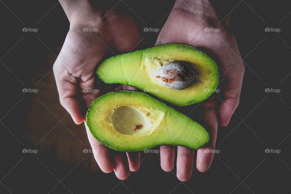 Hands holding avocado