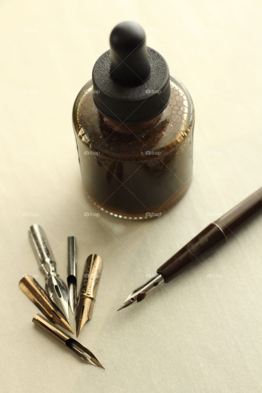 Arts & Crafts Supply - sepia ink bottle with various-sized metal nibs, nib in holder on parchment paper