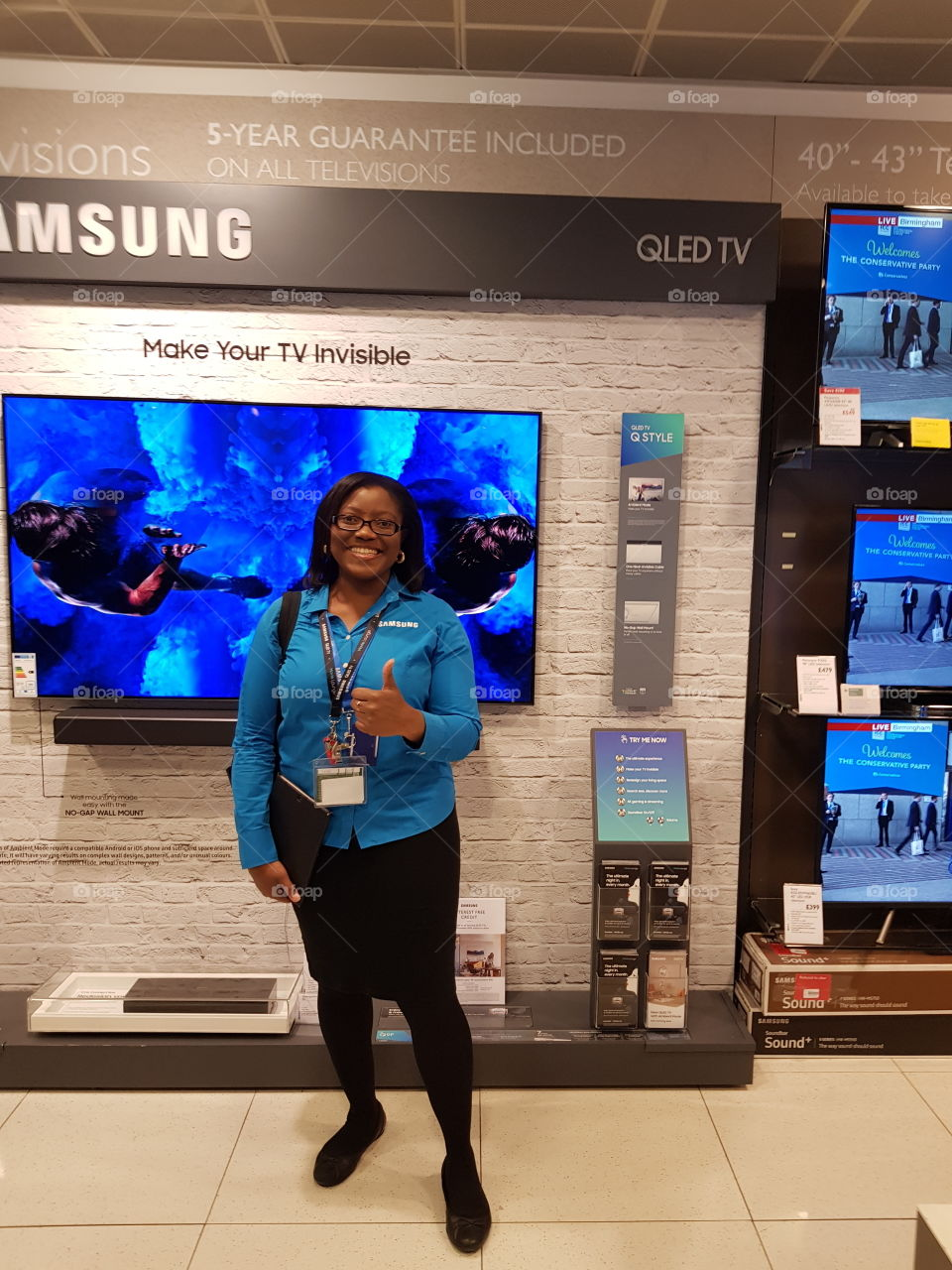 Antonia posing in front of the Samsung QLED television wall mounted with soundbar