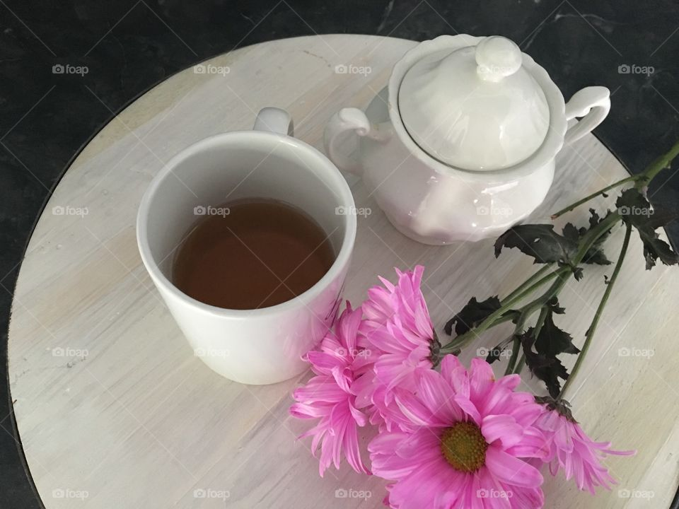 Pink flower with tea cup and teapot on table