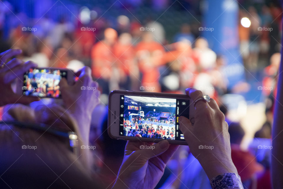 Women taking Photos on their Phones of an Event