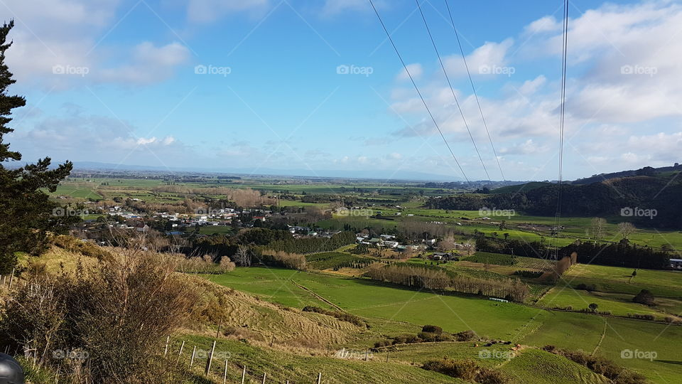 view on top of a hill over looking a town near to the sea. New Zealand