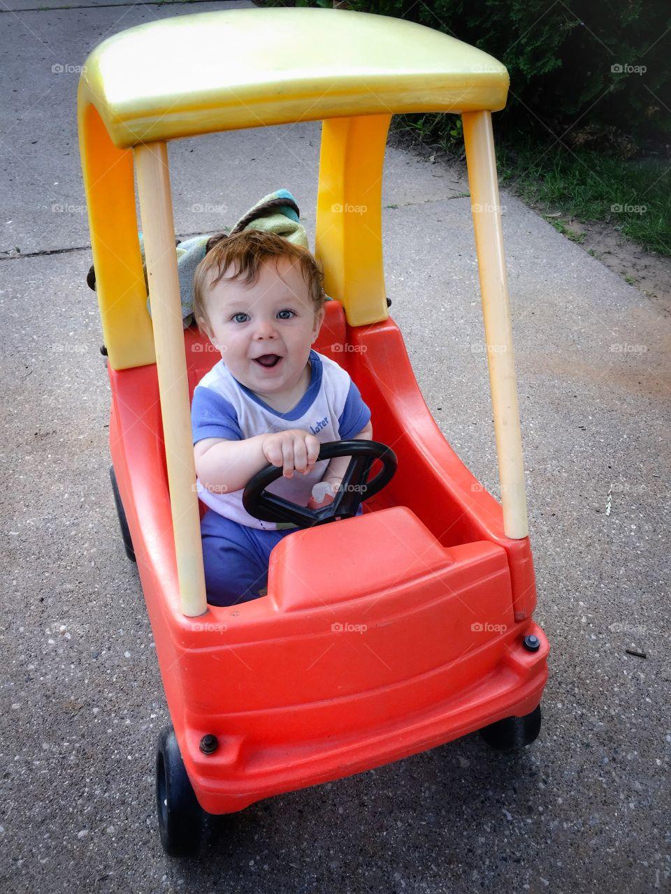 Cute boy travelling in toy car