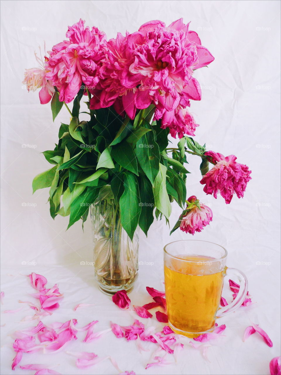 pink bouquet of wilted peony flowers and a cup of green tea