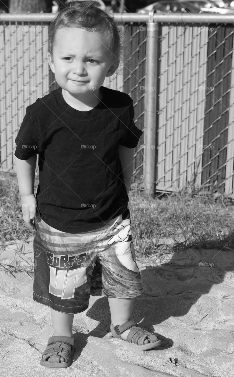 A small boy in shorts, t-shirt, and sandals stands in a sand pit with focused attention.