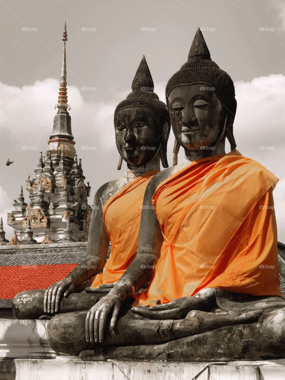Twin Buddha images in a temple with pagoda seen in backgrounds