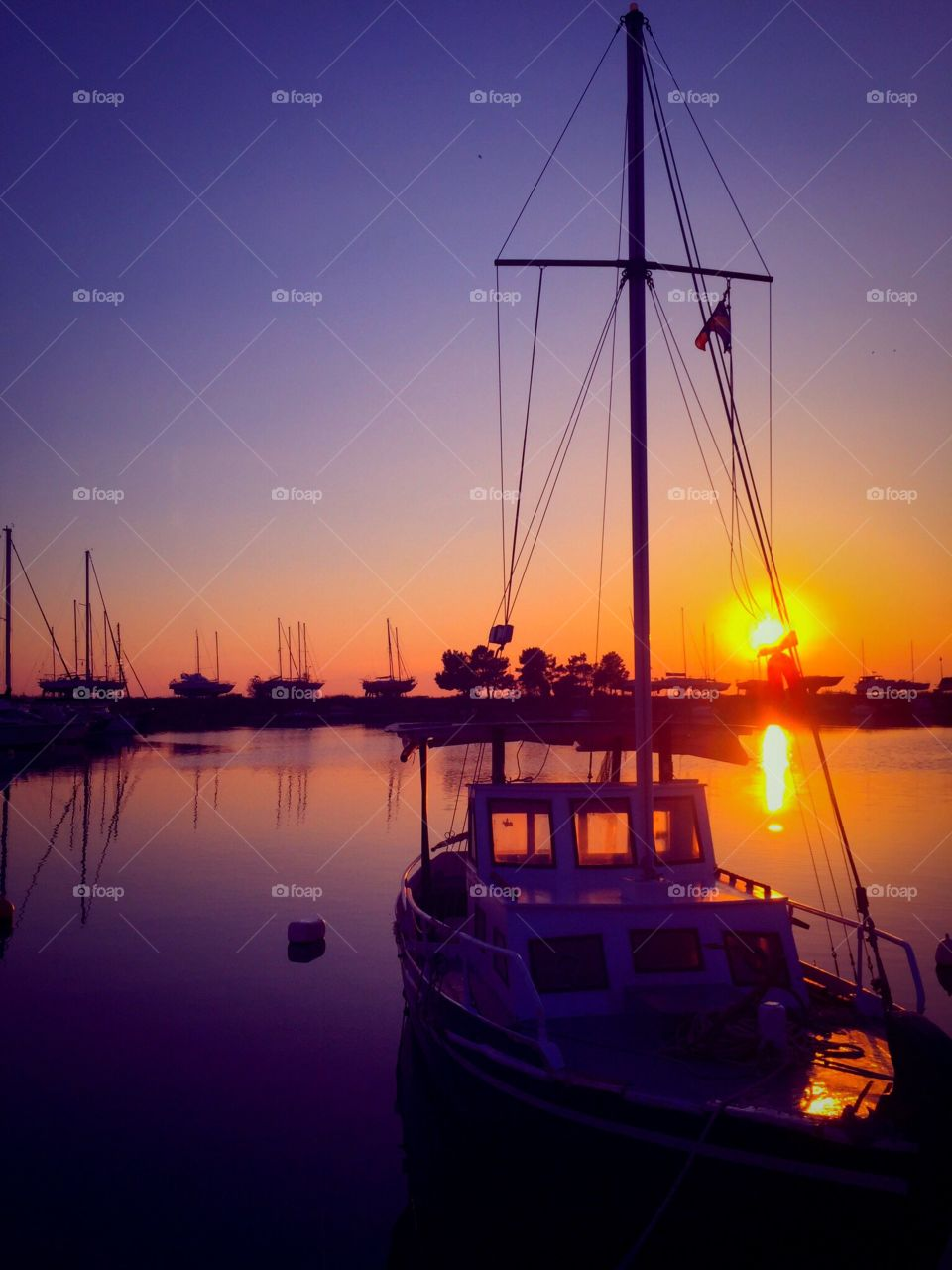 Boats moored at harbor at dusk