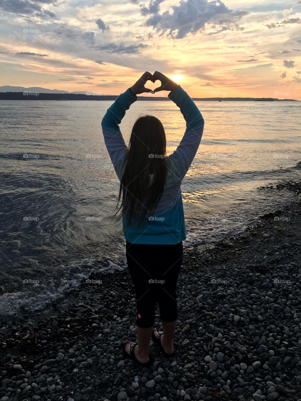 Gorgeous photo of young girl putting her hands together to form a heart with beautiful sunset in front of her!