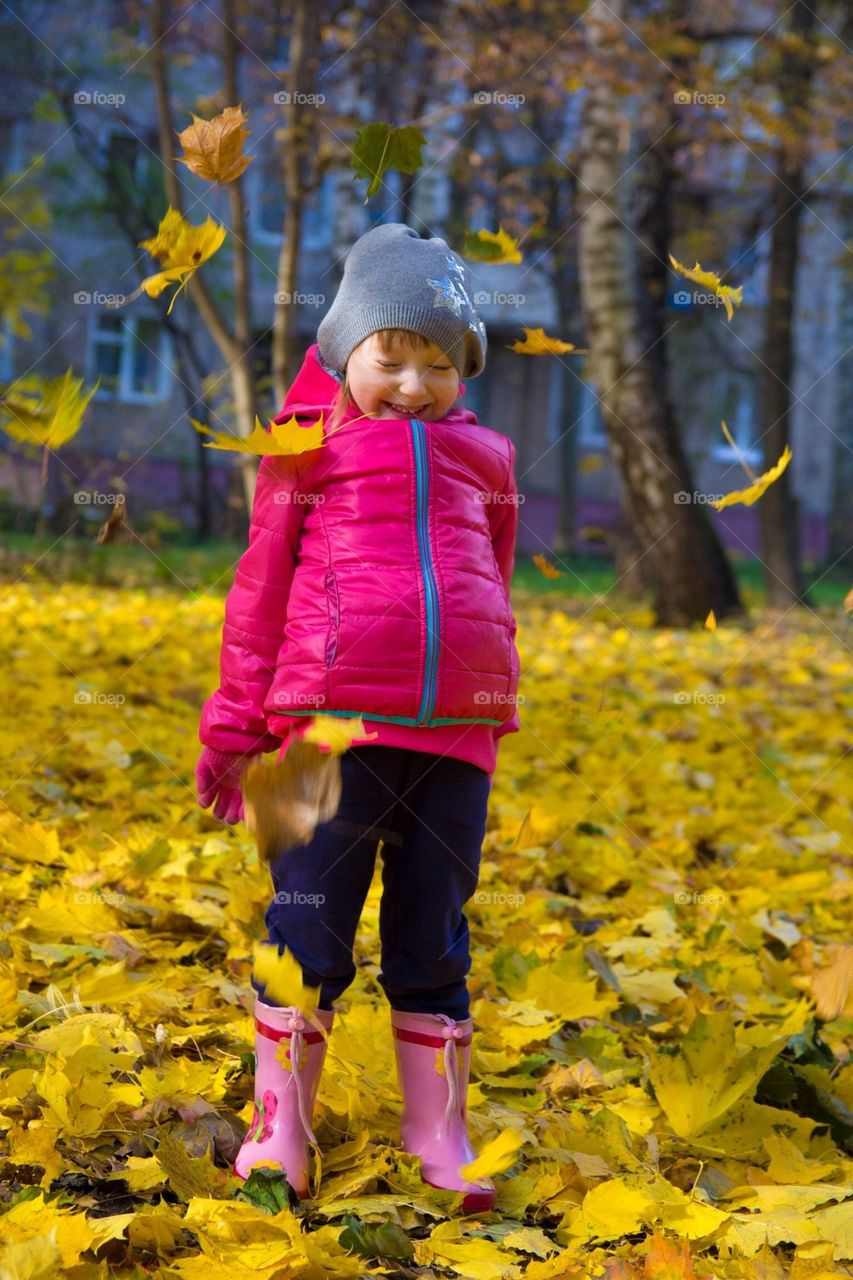 A child is playing witch the fallen leaves