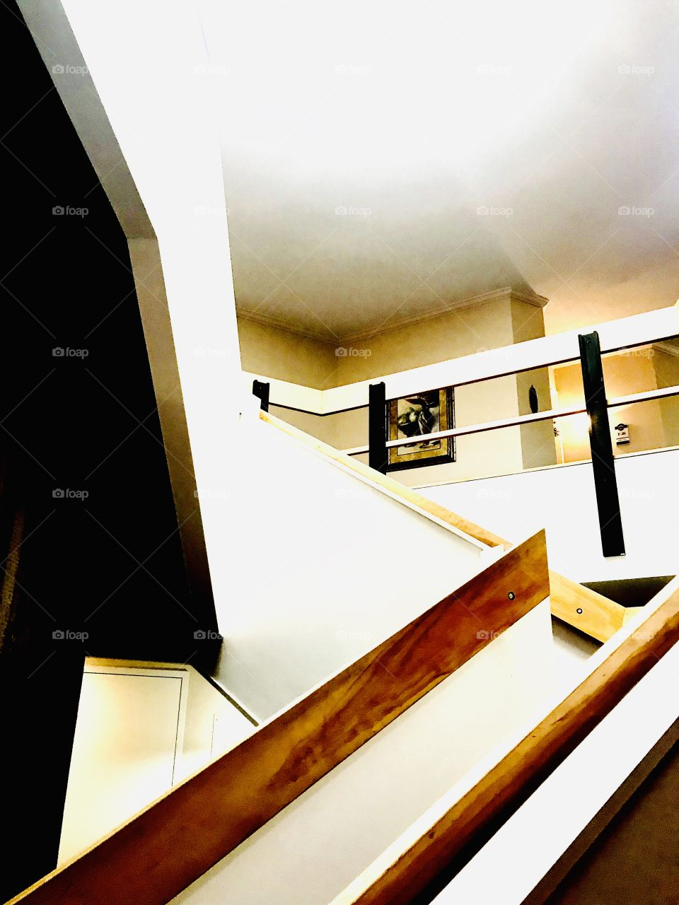 Architectural photo of a white and brown stairway with a turn in it makes for a fun photo!