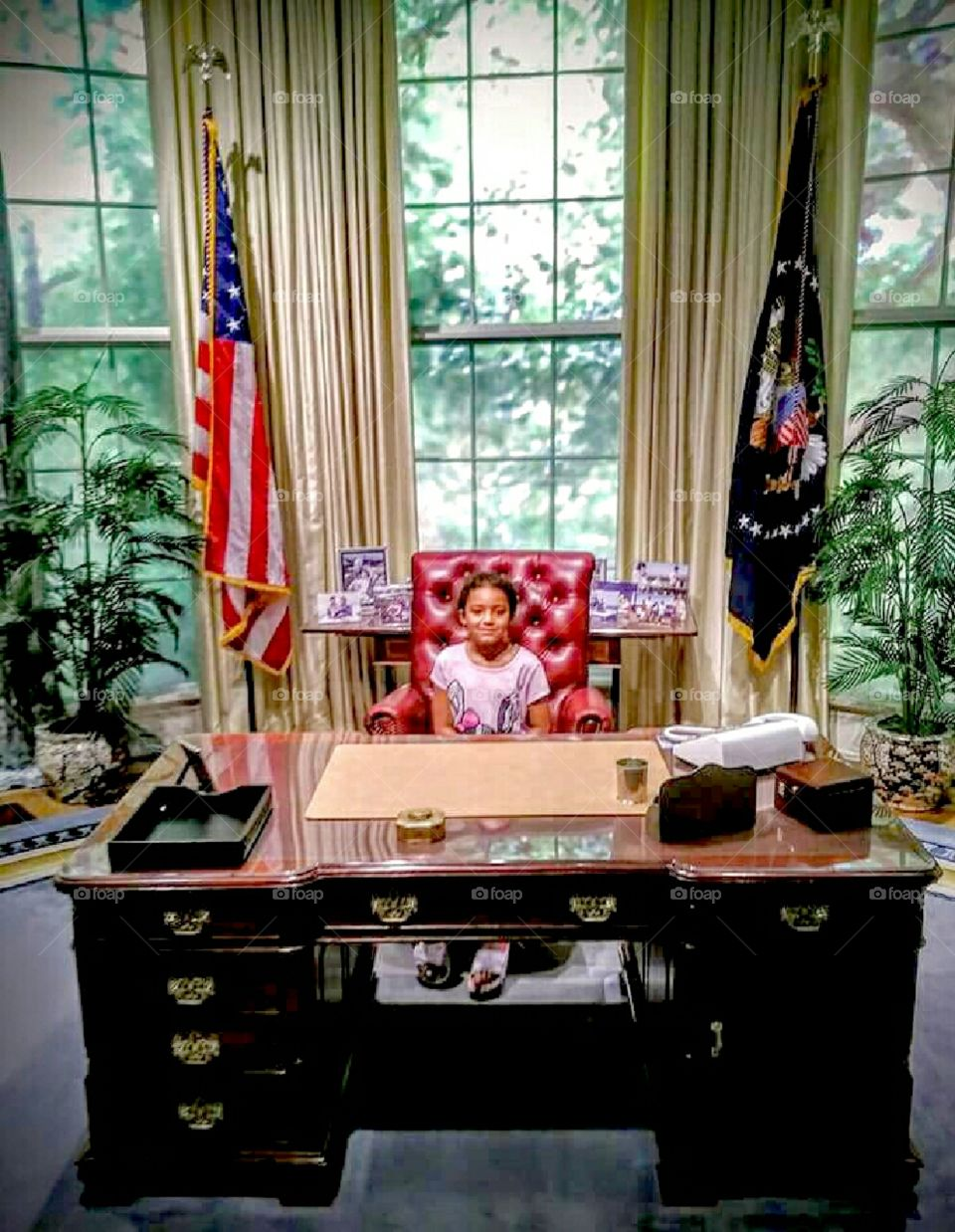 Girl sitting at Presidential Desk.   Who will be out next President?
