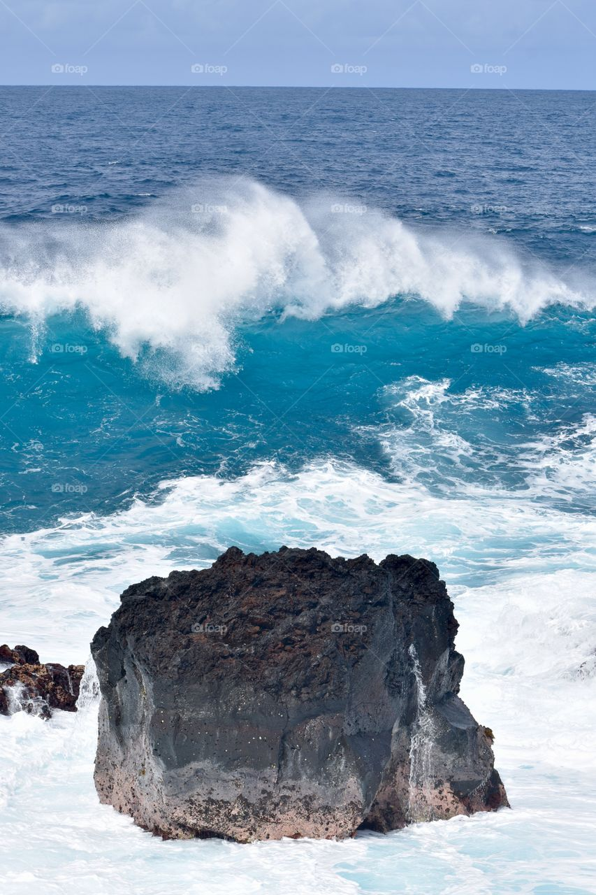 Big wave headed to the shore and the large lava rock in between.